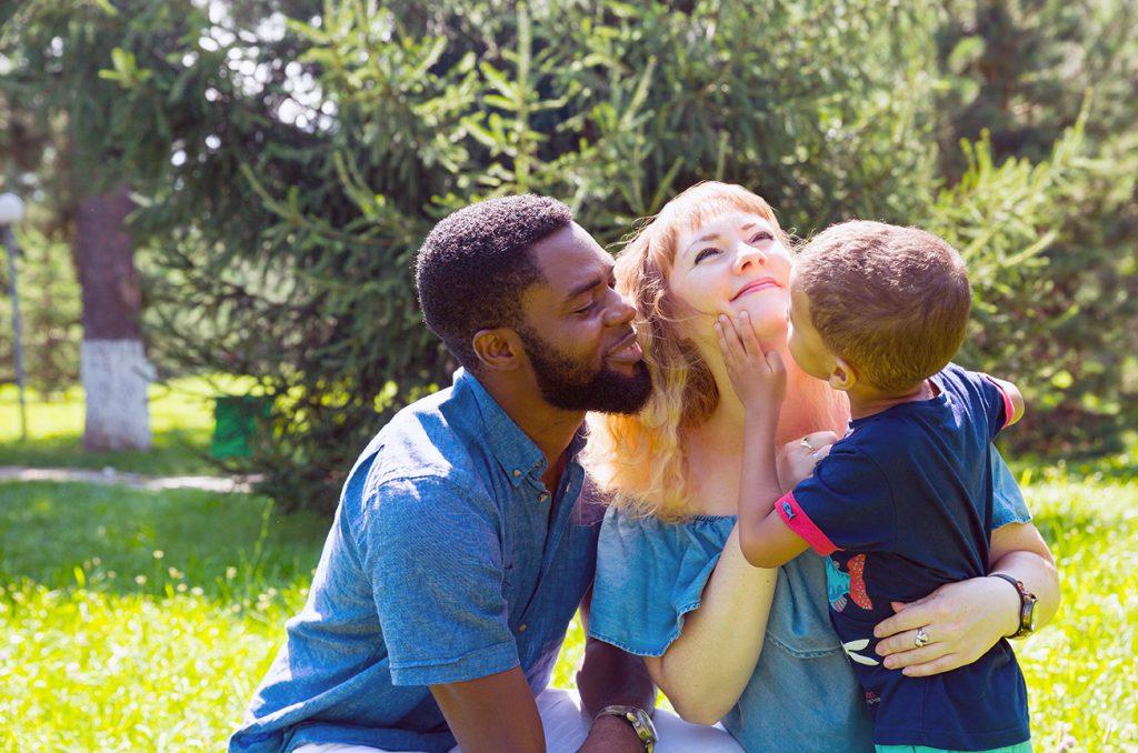 vader en moeder met hun kind zitten buiten op het gras voor een kansrijke start van hun zoon